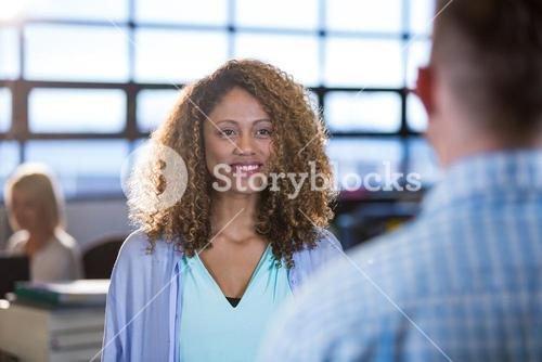 Businesswoman standing in front of male coworker