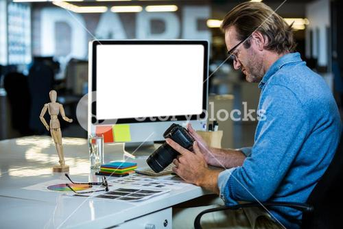 Creative businessman holding camera at computer desk