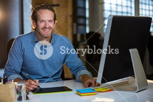 Confident photo editor working at desk