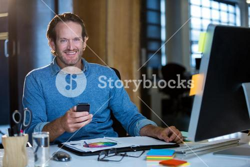 Businessman with cellphone at computer desk