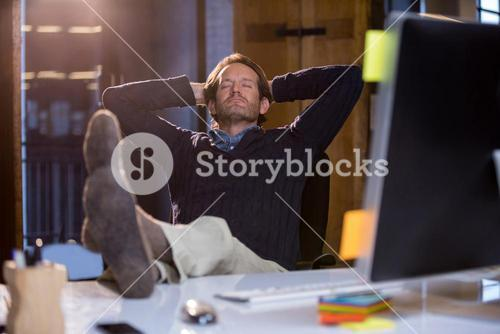 Businessman relaxing on chair at computer desk