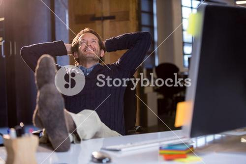 Businessman smiling while relaxing by desk
