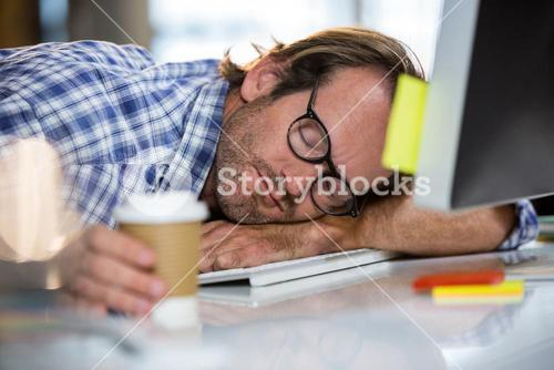 Businessman napping on computer desk