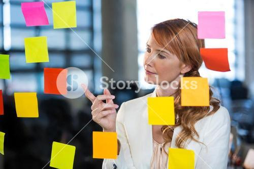 Businesswoman pointing at sticky notes