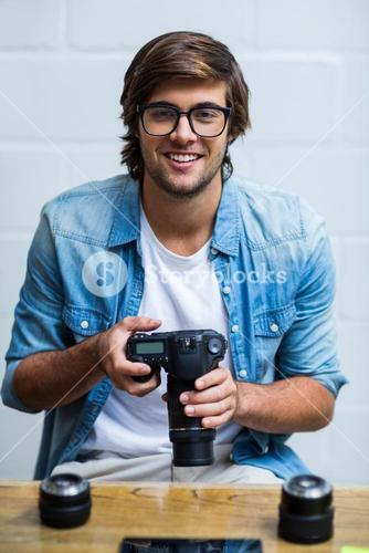 Portrait of happy man holding camera in office