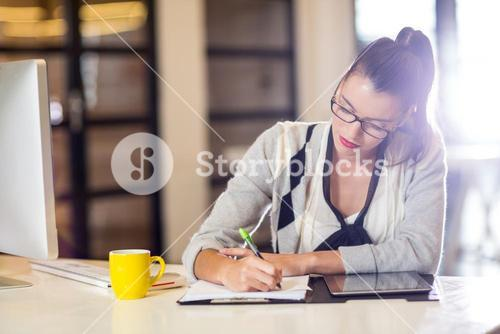 Woman writing on paper in office