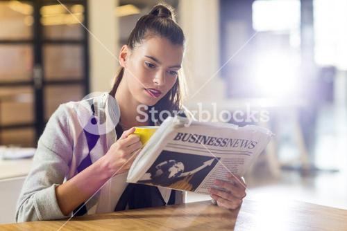 Woman reading newspaper in office