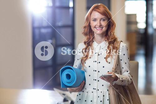 Portrait of woman holding mobile phone and folded mat