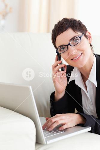 Businesswoman lying on a sofa with a laptop and a phone wearing glasses