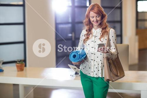 Smiling woman using phone while holding mat in office