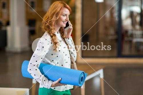 Smiling woman talking on phone while holding folded mat