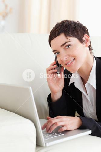 Cute Businesswoman lying on a sofa with a laptop and a phone