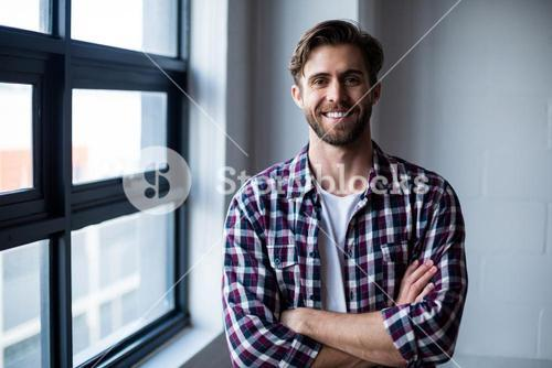Portrait of smiling man with arms crossed in office