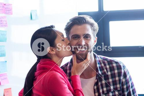 Woman kissing male colleague in office