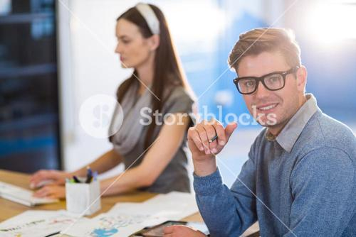 Businessman by colleague working at desk