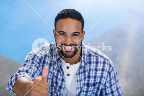 Businessman gesturing thumbs up in office