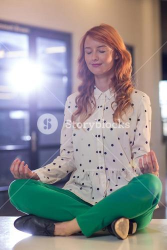 Young businesswoman doing yoga in office