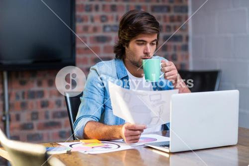 Businessman having coffee in office