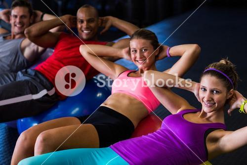 Portrait of smiling friends with hands behind back while stretching
