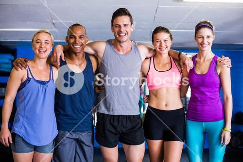 Portrait of smiling friends with arm around in gym