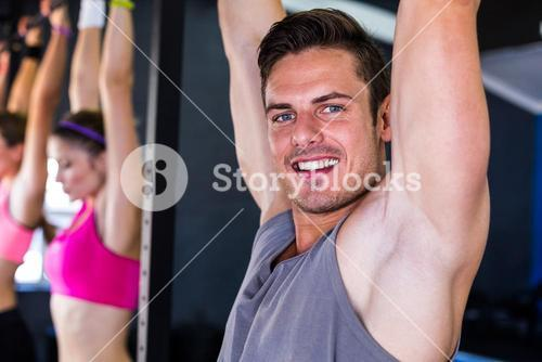 Portrait of smiling man doing chin-ups in gym