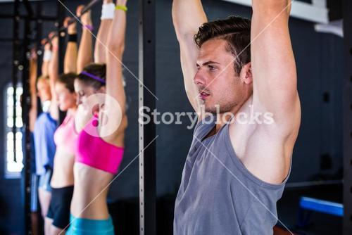 Man doing chin-ups in gym
