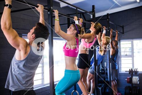 People doing chin-ups while exercising