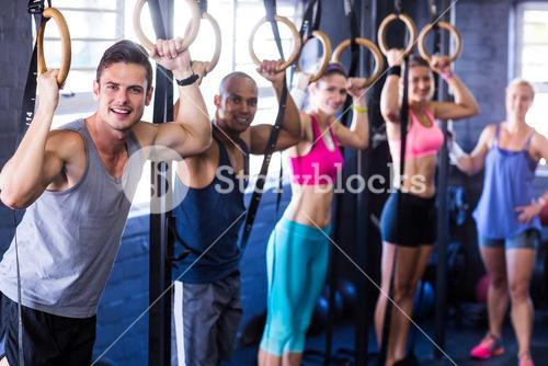 Portrait of smiling people with gymnastic rings