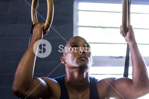 Close-up of man using gymnastic rings in gym