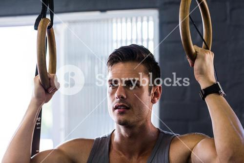 Close-up of young man using gymnastic rings in gym