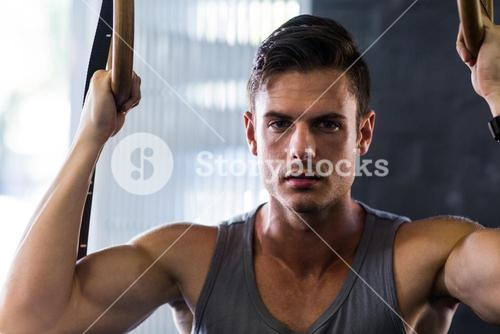 Portrait of young man using gymnastic rings in gym