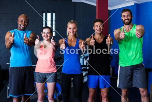 Smiling multi-ethnic friends showing thumbs up in gym