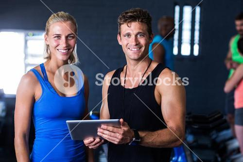 Portrait of smiling friends with digital tablet in gym