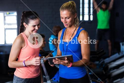Smiling friends with digital tablet in gym