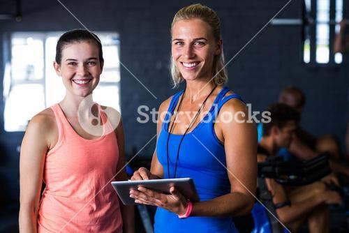Portrait of happy friends with digital tablet in gym