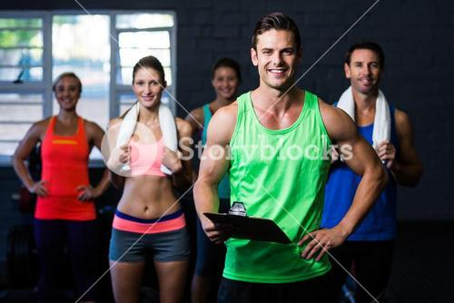 Smiling fitness instructor holding clipboard while people standing in background