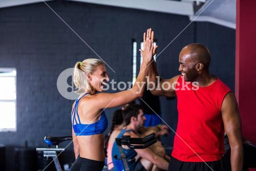 Smiling friends giving high-five in gym