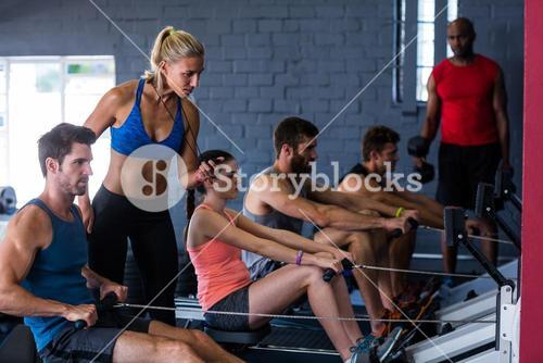 People using rowing machine with fitness instructor in gym