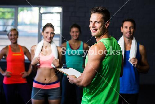 Portrait of cheerful fitness instructor with people in gym