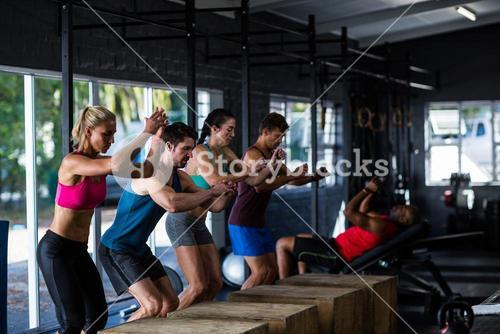 People leaning on wooden cubes in gym