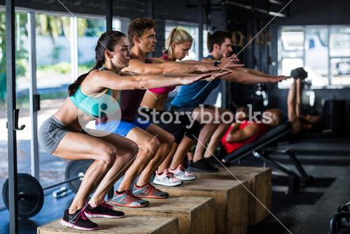 People stretching while standing on wooden cubes