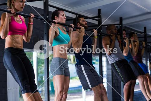 Young friends doing chin-ups in gym