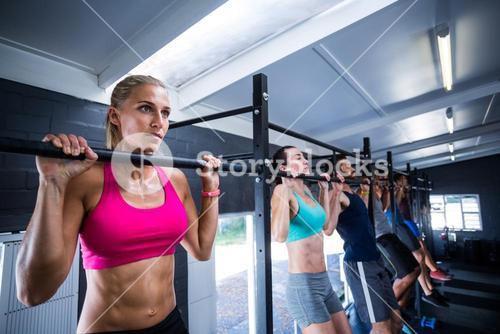 Athletes doing chin-ups in gym