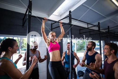 Smiling friends cheering woman doing chin-ups in gym