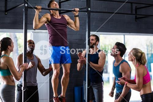 Friends cheering young man doing chin-ups