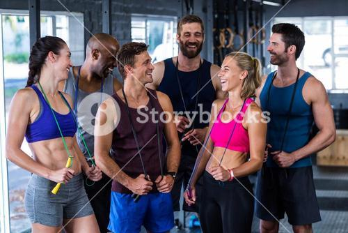 Smiling friends with jumping ropes in gym