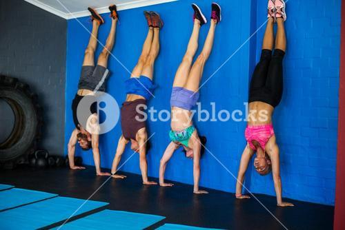 Athletes doing handstand against wall