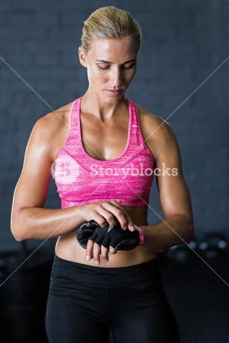 Female athlete removing gloves against wall in gym