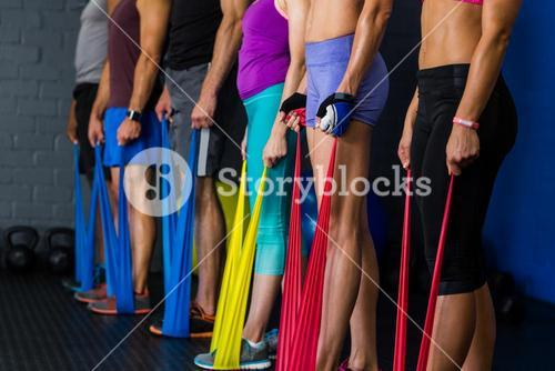 Athletes with resistance band in gym