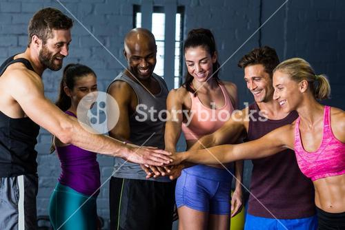 Athletes stacking hands in gym